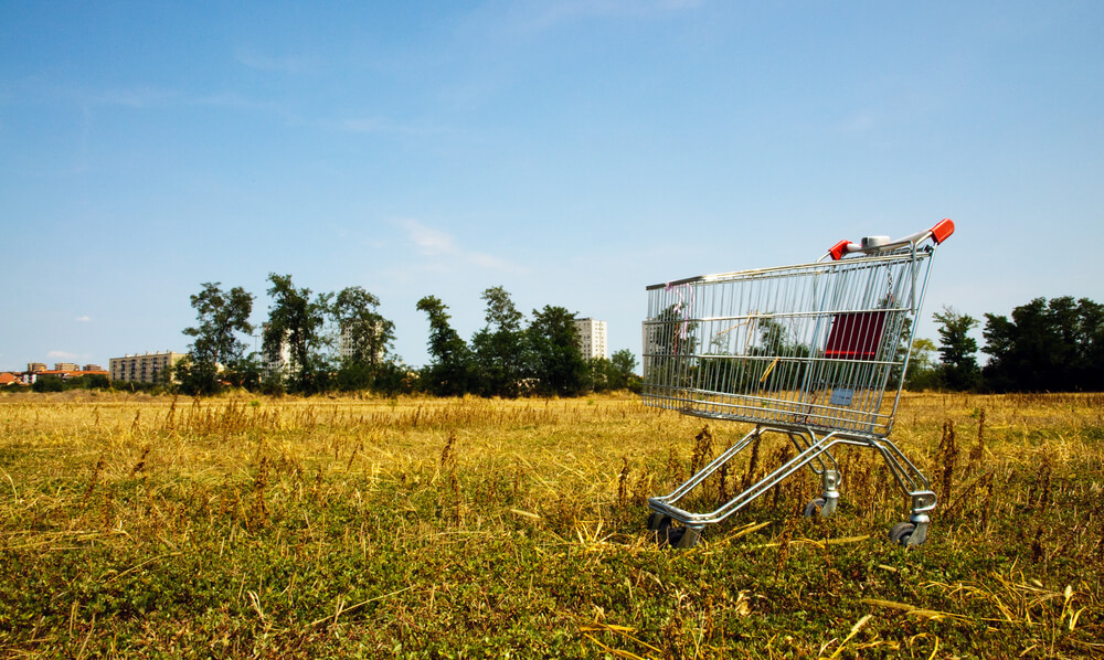 An empty shopping cart in a field