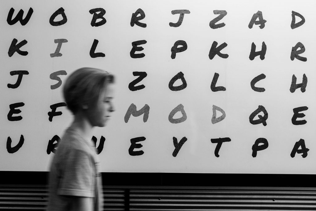 A young boy walking past a wall with random black letters on it
