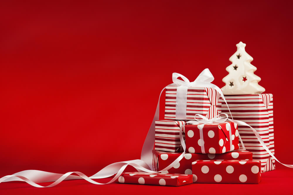 Christmas presents with red wrapping paper against a red background
