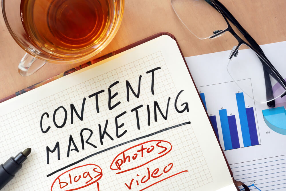 """A notebook with the words """"Content Marketing"""" on a cluttered desk"""