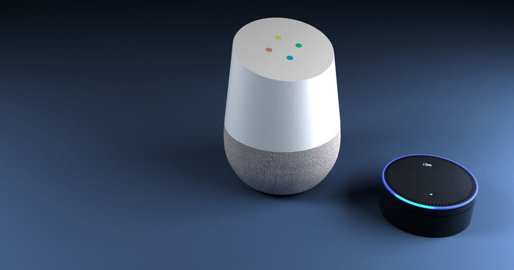 A Google Home device sitting next to an Amazon Alexa device