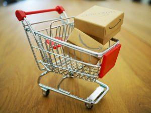 A mini shopping cart with two mini Amazon boxes inside