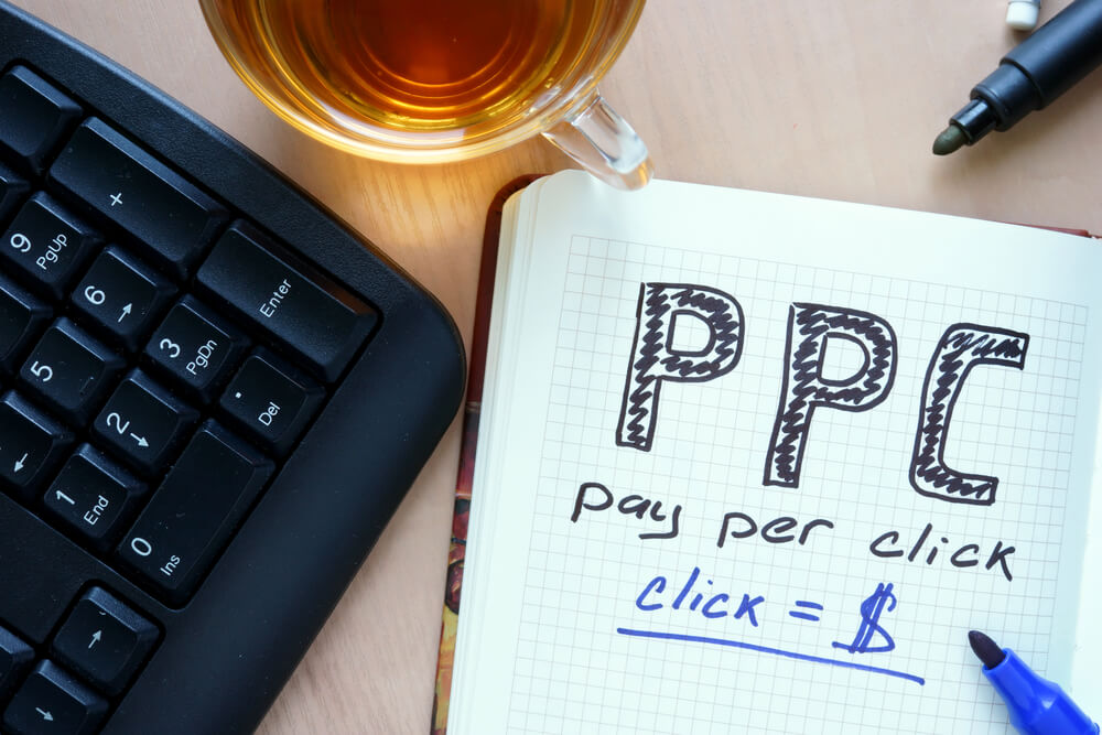 "The words ""PPC"" and ""pay per click"" written on a notebook."