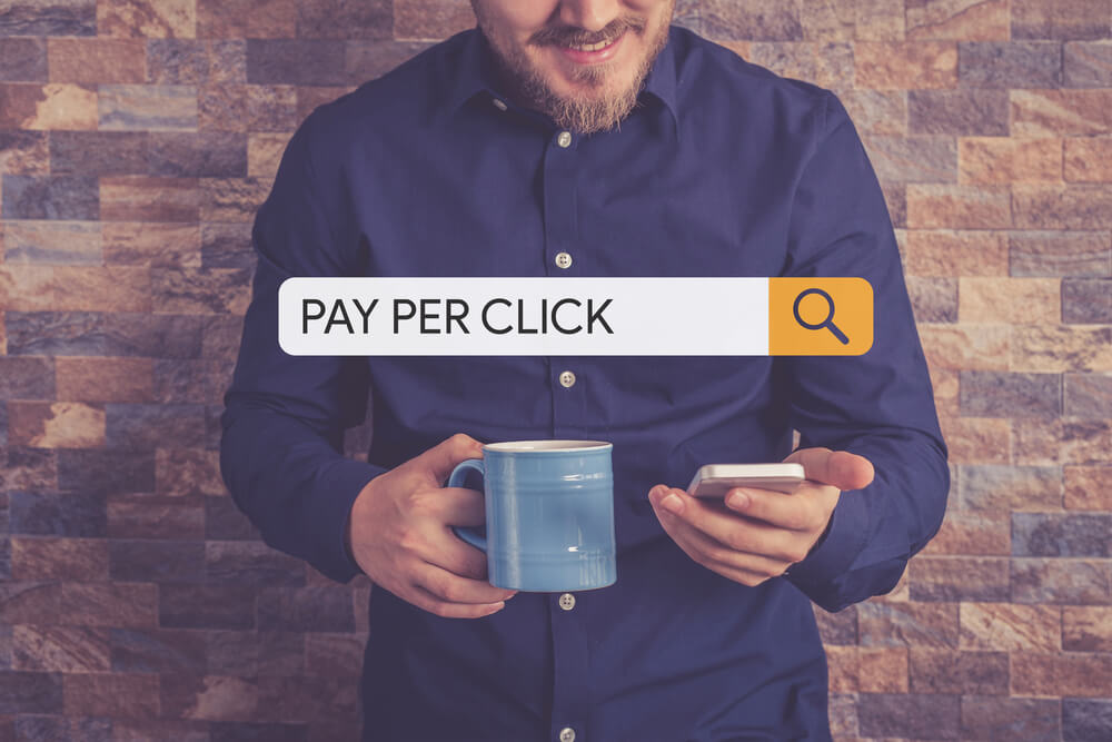 "a search bar with ""PAY PER CLICK"" typed in and a guy looking at his phone in the background"