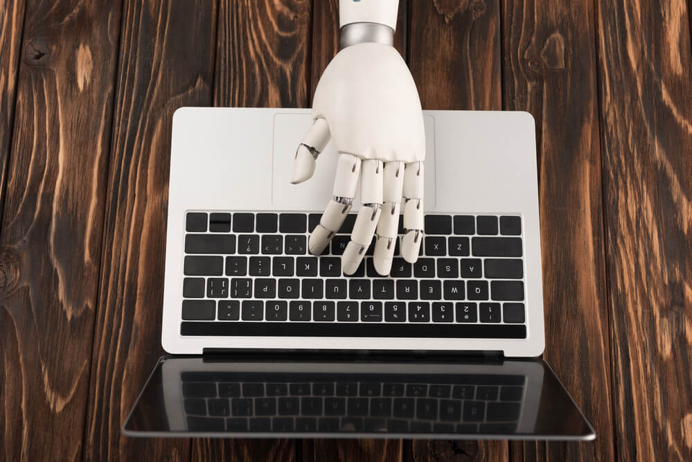 A robotic hand typing on a keyboard